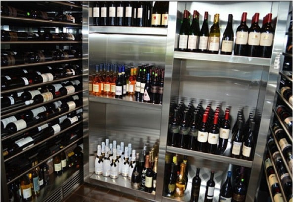 A wine cellar with a cooling unit by US Cellar Systems